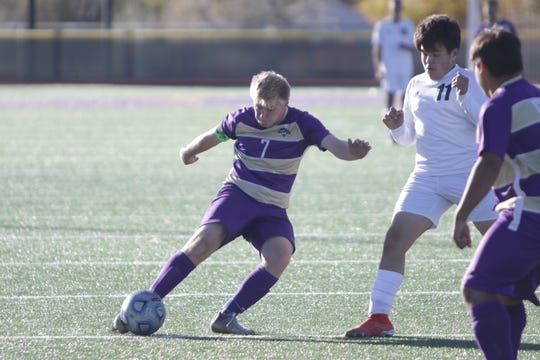Kirtland Central's Colten Warner fires a shot against Aztec's Coby McClain during a District 1-4A boys soccer match on Thursday, Oct. 24 at Bill Cawood Field in Kirtland.