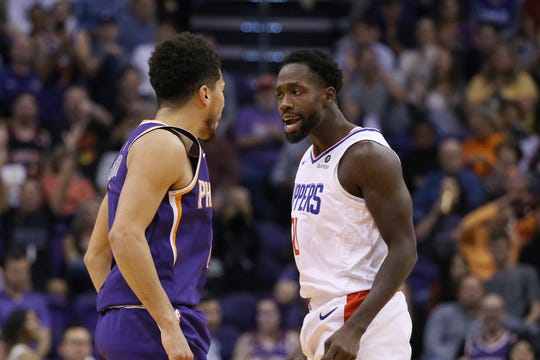LA Clippers guard Patrick Beverley jaws with Phoenix Suns guard Devin Booker, left, after a Booker score during the second half of a basketball game Saturday, Oct. 26, 2019, in Phoenix. The Suns defeated the Clippers 130-122. (AP Photo/Ross D. Franklin)