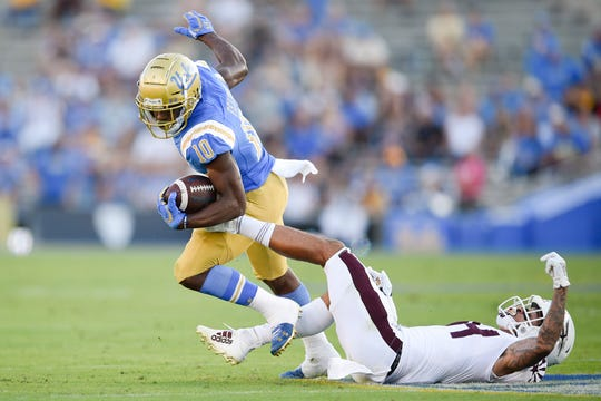 Oct 26, 2019; Pasadena, CA, USA; UCLA Bruins running back Demetric Felton (10) runs past Arizona State Sun Devils defensive back Chase Lucas (24) during the first half at Rose Bowl. Mandatory Credit: Kelvin Kuo-USA TODAY Sports