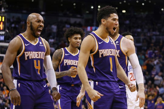 Phoenix Suns guard Devin Booker (1) celebrates his score against the LA Clippers with Suns guard Jevon Carter (4) during the second half of a basketball game Saturday, Oct. 26, 2019, in Phoenix. The Suns defeated the Clippers 130-122. (AP Photo/Ross D. Franklin)