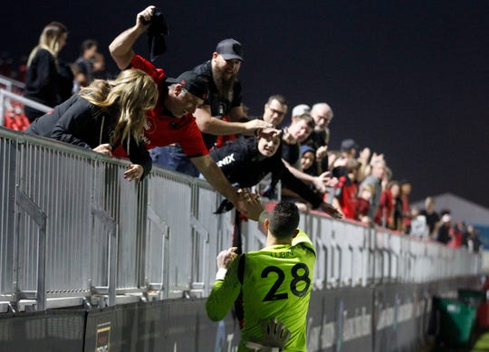 Phoenix Rising fans slap high fives with goalie Zac Lubin after their overtime shootout win over Austin Bold at Casino Arizona Field.