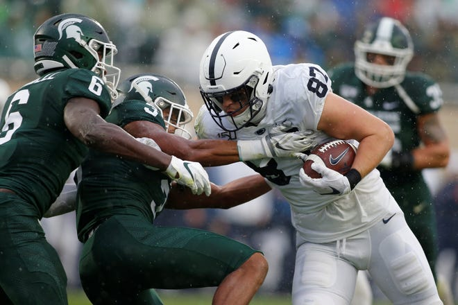 Penn State's Pat Freiermuth, right, pushes past Michigan State's Xavier Henderson (3) and David Dowell (6) for a touchdown during the second quarter of an NCAA college football game, Saturday, Oct. 26, 2019, in East Lansing, Mich. (AP Photo/Al Goldis)