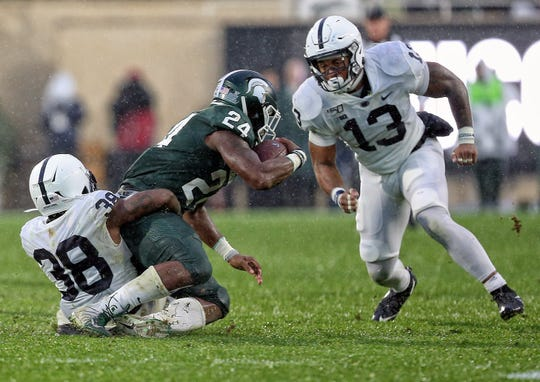Oct 26, 2019; East Lansing, MI, USA; Michigan State Spartans running back Elijah Collins (24) is tackled by Penn State Nittany Lions safety Lamont Wade (38) during the second half of a game  at Spartan Stadium. Mandatory Credit: Mike Carter-USA TODAY Sports