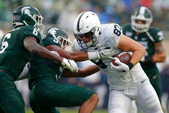 Penn State's Pat Freiermuth pushes past defenders for a touchdown against Michigan State.