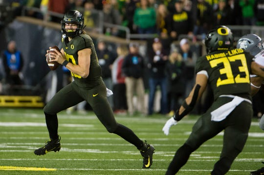 Oct 26, 2019; Eugene, OR, USA; Oregon Ducks quarterback Justin Herbert (10) rolls out to pass the ball against the Washington State Cougars during the first half at Autzen Stadium. Mandatory Credit: Troy Wayrynen-USA TODAY Sports