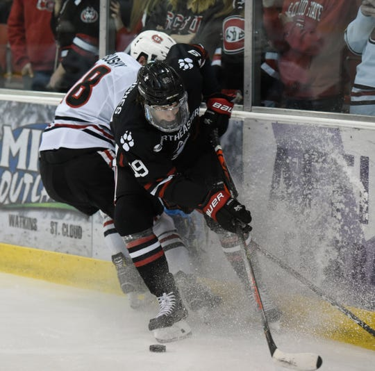 SCSU sophomore Brendan Bushy fights for the puck against Northeastern Saturday, Oct. 26, 2019, at Herb Brooks National Hockey Center.