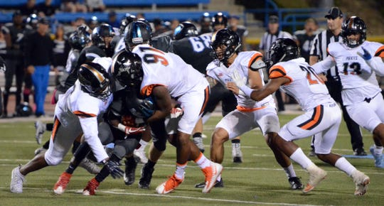 Moorpark College running back Brandon Archibald is engulfed by the Ventura College defense, including defensive end Darius Johnson (91), in the 52nd Citrus Cup game last Saturday night at Griffin Stadium. VC won 55-20.
