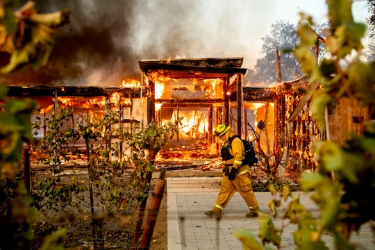 Woodbridge firefighter Joe Zurilgen passes a burning home as the Kincade Fire rages in Healdsburg, Calif., on  Oct 27, 2019.