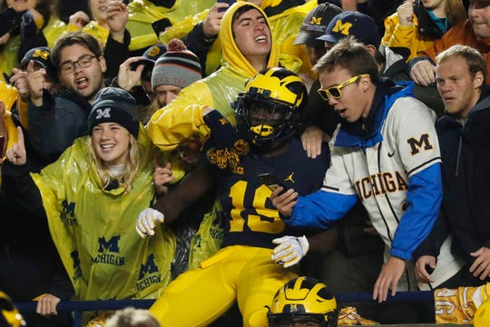 Michigan Wolverines wide receiver Mike Sainristil celebrates with the student section after the game against the Notre Dame Fighting Irish at Michigan Stadium.