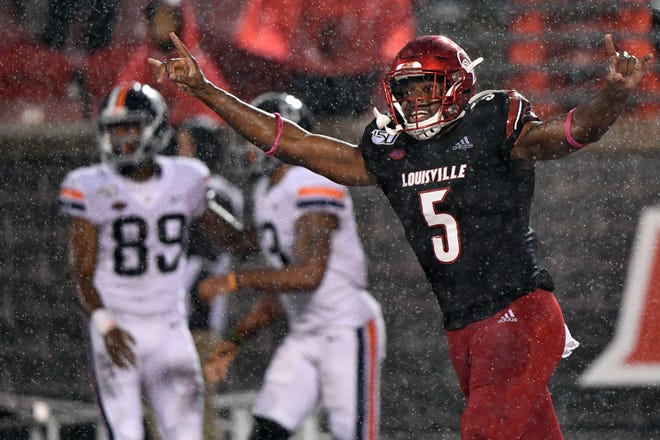 Louisville Cardinals linebacker Robert Hicks (5) celebrates after time runs out against the Virginia Cavaliers at Cardinal Stadium.