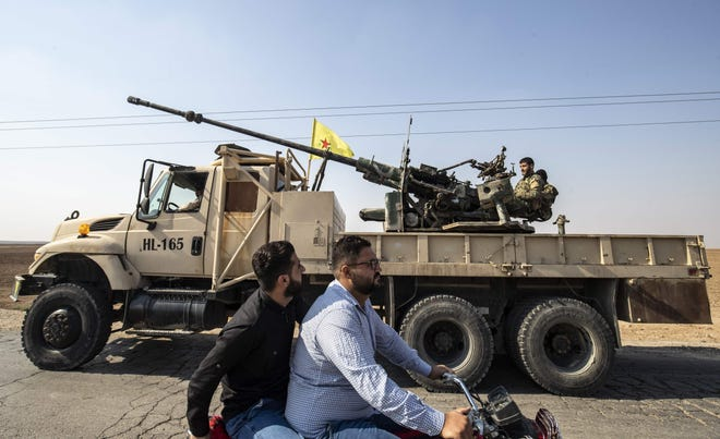 Fighters from the Syrian Democratic Forces (IDF) atop a military vehicle prepare to withdraw from the Sanjak Saadoun border area near the northern Syrian town of Amuda, on October 27, 2019. - Kurdish forces today said they will redeploy away from the entire length of Syria's nothern border in compliance with a Russian-Turkish agreement that will see them replaced by Damascus-backed forces. (Photo by Delil SOULEIMAN / AFP) (Photo by DELIL SOULEIMAN/AFP via Getty Images) ORIG FILE ID: AFP_1LS3ND