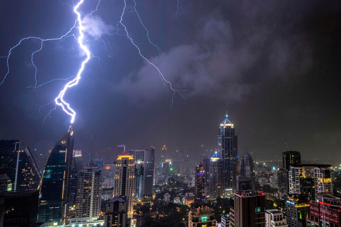 Lghtening strikes on a building during a thunderstorm in Bangkok on Oct. 27, 2019.