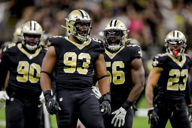 New Orleans Saints defensive tackle David Onyemata (93) and outside linebacker Demario Davis (56) celebrate after a turnover on downs against the Arizona Cardinals during the third quarter at the Mercedes-Benz Superdome.