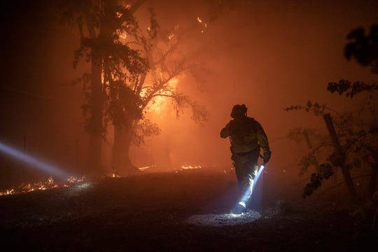 epa07953820 A firefighter walks pass a building burning out of control, as the Kincade Fire continues to burn in Healdsburg, California, USA, 27 October 2019.  According to reports, the Kincade Fire has burned more than 25,000 acres and triggered mandatory evacuations of about 90,000 residents in the area.  EPA-EFE/PETER DASILVA ORG XMIT: PDS01
