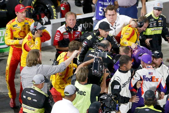 A fight between Denny Hamlin and Joey Logano is broken up.