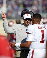 Oklahoma head coach Lincoln Riley talks to quarterback Jalen Hurts during the first quarter against Kansas State.