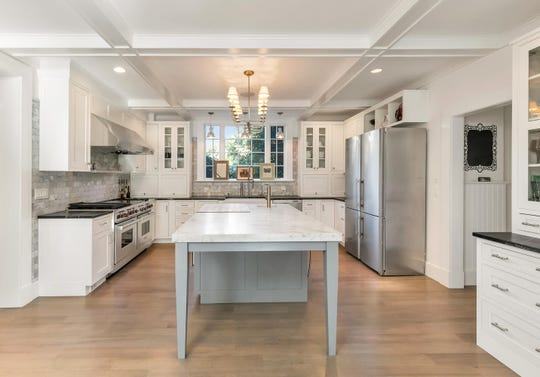 The kitchen features custom cabinetry Wolf range and two full-size ovens