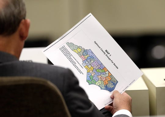 In this Wednesday, July 26, 2017 photo, a lawmaker holds a districting map during a joint select committee meeting on redistricting in Raleigh, N.C. North Carolina judges on Monday, Oct. 28, 2019 blocked the state's congressional map from being used in the 2020 elections, ruling that voters had a strong likelihood of winning a lawsuit that argued Republicans unlawfully manipulated district lines for partisan gain. (AP Photo/Gerry Broome)