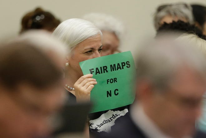 In this July 26, 2017 photo, a member of the gallery tries to display her sign while lawmakers convene during a joint select committee meeting on redistricting in Raleigh, N.C. North Carolina judges on Monday blocked the state's congressional map from being used in the 2020 elections, ruling that voters had a strong likelihood of winning a lawsuit that argued Republicans unlawfully manipulated district lines for partisan gain. (AP Photo/Gerry Broome)