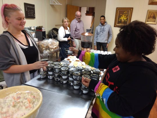 La-Toya Cornish, left, and Danita-Marie Smith, right, sort containers of yogurt at the weekly dinner held at First Presbyterian Church of Johnson City. The dinner is one of several outreach activities the church does as part of its This Day program.