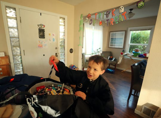 Azrael Early, 8, pulls a bag of Skittles out of the giant bag of Halloween candy at his Bremerton home. Azrael and his family will be giving the candy away to trick-or-treaters in downtown Bremerton on Halloween.