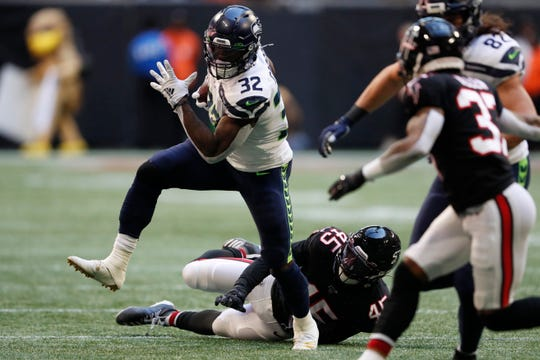Seattle Seahawks running back Chris Carson (32) runs against Atlanta Falcons linebacker Deion Jones (45) during the first half of an NFL football game, Sunday, Oct. 27, 2019, in Atlanta. (AP Photo/John Bazemore)