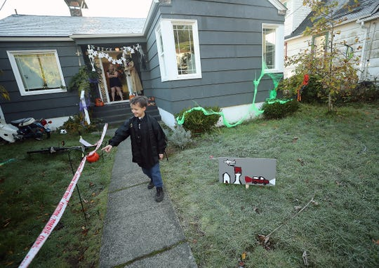 Azrael Early, 8, shows off the Halloween decorations adorning the front yard of his Bremerton home on Monday.