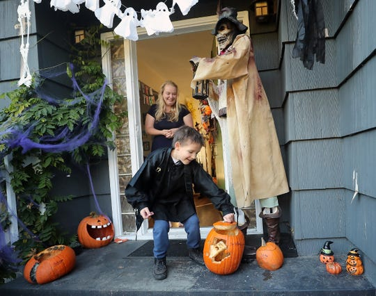Azrael Early, 8, places the lid on his pumpkin as his mother, Jessie, looks on from the front door of their Bremerton home on Monday. Azrael's fight with cancer has made it difficult for him to fully participate in Halloween, but a special request will put him front-and-center for trick-or-treaters in downtown Bremerton this year.