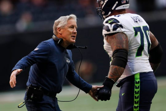 Seattle Seahawks head coach Pete Carroll speaks to players during the first half of an NFL football game against the Atlanta Falcons, Sunday, Oct. 27, 2019, in Atlanta. (AP Photo/John Bazemore)