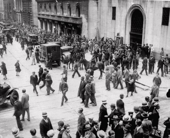 Crowds move past the New York Stock Exchange, second building from right, on New York's Wall Street at the height of the stock market crash, Oct. 24, 1929, as policemen on horseback keep the throng moving.