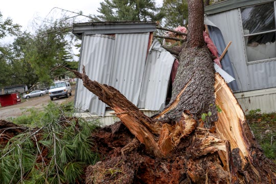 An uprooted tree lays where it crushed a home nearly in half at a mobile home park on Power Street in Clarksville, Tenn., on Monday, Oct. 28, 2019.
