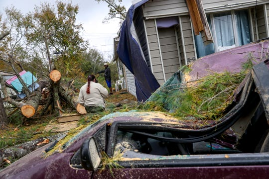 Carmen Ruiz and Angel Castro walk back to review damage sustained to their home and vehicles at a mobile home park on Power Street in Clarksville, Tenn., on Monday, Oct. 28, 2019.