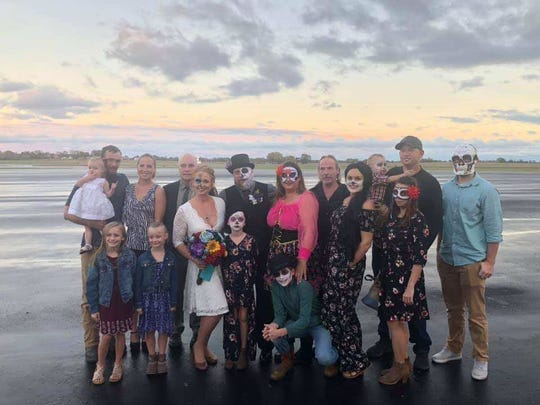 Jarrod and Jenn Maloney pose with their friends and family after a storm destroyed much of their airport wedding venue on Oct. 26, 2019.