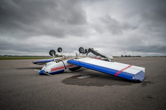 An airplane lies upside down at the Clarksville Regional Airport after Saturday's storm blew through the area, causing massive damage.