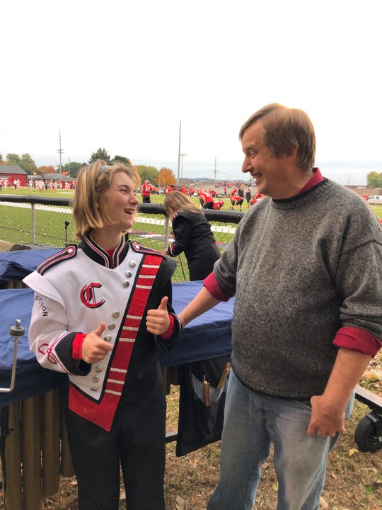 Lacey Richcreek and Barry Hardesty, band director for Coshocton High School, share a moment before the pregame show began at Stewart Field recently.