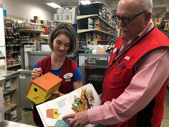 """Lacey Richcreek and Tom Edwards show off the birdhouse that Lacey painted to go along with the """"Let's Go to the Hardware Store"""" books that children receive when they visit Auer Ace Hardware."""