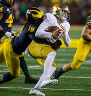 Luiji Vilain tackles Notre Dame quarterback Phil Jurkovec in the fourth quarter of Michigan's 45-14 win Oct. 26, 2019, in Ann Arbor.