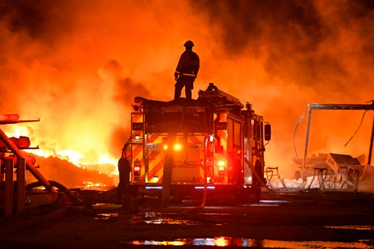 A firefighter stops to look at a wall of fire while battling a grass fire on East Cypress Road in Knightsen, Calif., on Sunday, Oct. 27, 2019. The grass fire originated 3:08 a.m. on Gateway Boulevard on Bethel Island as reported by the East Contra Costa Fire Department. The fire then spread to a second location on East Cypress Road at 5:45 a.m.
