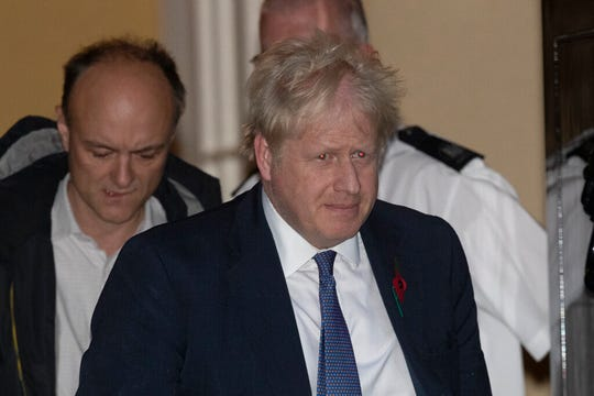 British Prime Minister Boris Johnson and his advisor Dominic Cummings, left, leave 10 Downing Street in London, and get in a car together to go to the Houses of Parliament, Monday, Oct. 28, 2019.  Johnson says it's Parliament's fault, not his, that Britain will not be leaving the European Union as scheduled on Oct. 31. The EU has agreed to postpone Brexit until Jan. 31, 2020, after Johnson failed to get British lawmakers to ratify his divorce deal with the bloc in time to leave this week.