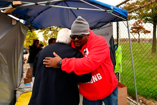 Local 22 workers Nick Wojnarowski, left, and James Reynolds hugged each other  at the Detroit-Hamtramck Assembly plant as the six-week strike against General Motors came to a close Friday.