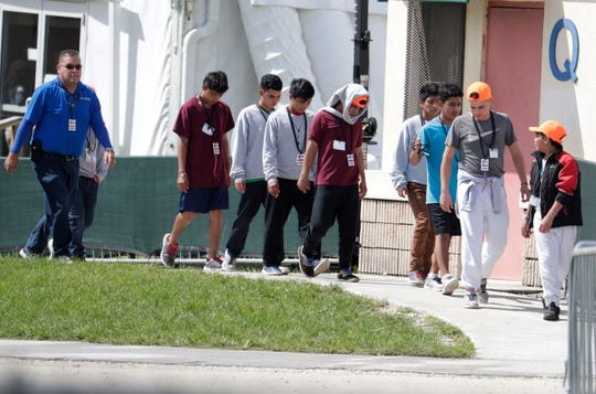 Migrant children walk on the grounds of the Homestead Temporary Shelter for Unaccompanied Children July 15 in Homestead, Fla.