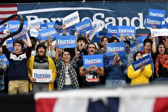 People standing behind the stage cheer while Sen. Bernie Sanders speaks.
