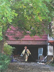 A  firefighter walks out of a home on the 700 block of Fisher in Grosse Pointe.