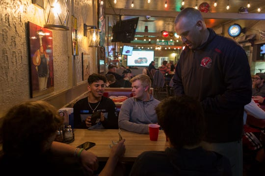 Livonia Franklin football players Hasan Alwan, left, and Jake Kelbert, 17, talk while football coach Chris Kelbert, collects money for pizza during the team's watch party at Benny's Pizza on Sunday.
