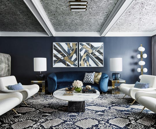Low ceiling? Greg Natale's solution: Create a little drama. He first papered the tray ceiling in a swirling malachite pattern in black and white, painted the walls navy and furnished the space with a blue velvet sofa by Kelly Wearstler, paired with white Cassina chairs. The snakeskin rug by Diane von Furstenberg is genius. And the final touch: graphic prints with glint of gold.