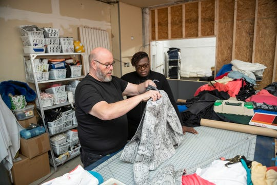 Benson Roberts III, left, talks with apprentice Christian LeRone in the workshop of the Detroit Fabric Company in Detroit.