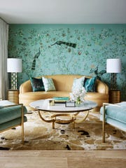 "A hand-painted de Gournay wallcovering is paired with the organic Ink rug from Greg Natale's collection. The rug's warm tones carry over to the curved camel leather Dorothy Draper sofa and brass frame of the vintage coffee table, from Conley and Co., and the frame of the two chairs upholstered in velvet. This use of pattern is one of the designer's favorites, especially the vivid scene of birds that are both delicate and compelling. It's ""pattern as its most extravagant,"" Natale says."