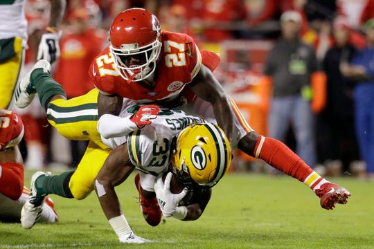 Green Bay Packers running back Aaron Jones (33) is tackled by Kansas City Chiefs cornerback Rashad Fenton (27) during the first half on Sunday.