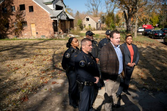 Representatives from the Detroit Building Authority and police department assemble for a press conference to discuss a blight removal program taking place in the neighborhood just east of the state fairgrounds in Detroit, Monday.