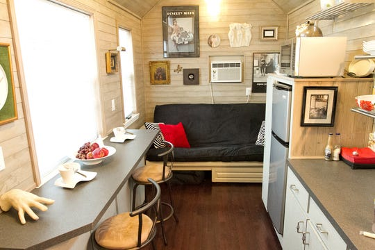 : If homeowners are investing in tiny houses, they want to utilize every square inch of space within. This tiny home kitchen features both a bar and comfortable seating area.